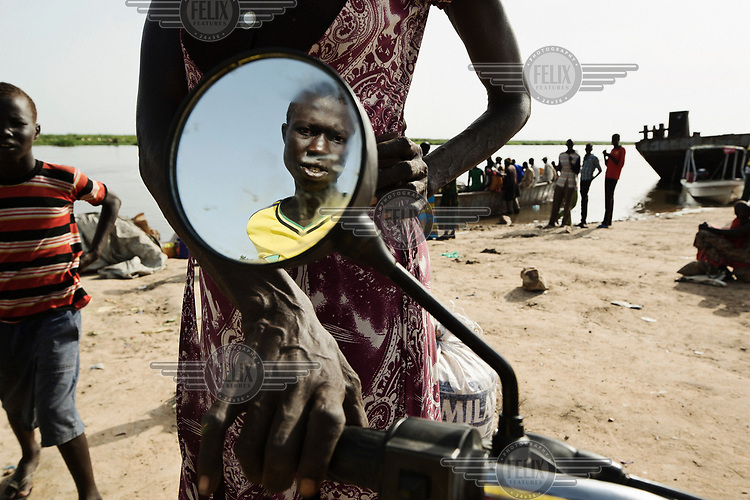 A man reflected in a motorcycle's mirror parked at a landing site on the White Nile.