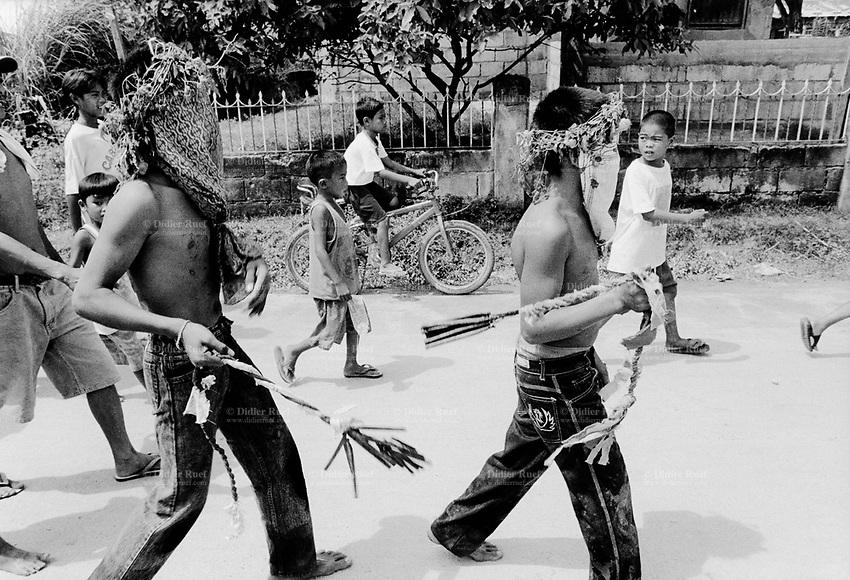 Philippines. Luzon island. San Fernando, Pampanga.70 km from Manila. Flagellation at Easter on Good Friday. Masked boys walk on the main street.  © 1999 Didier Ruef