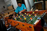 A carpentry worker polishes the player figures with a rag at a table football workshop in Quito, Ecuador, 2 March 2012. Table football, also known as futbolin in Latin America, is a widely popular table-top game in Ecuador. During the annual fairs, the rusty old outdoor-designed tables, fully ocuppied by excited children, may be found on all public places, particularly on the squares and in the parks. Although there have always been several small table football workshops in all large Ecuadorean towns, the table football craft and tradition is on a decline in last years, mainly due to the video-game boom.