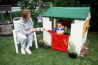 Intergenerational: Grandmother and grandson in child's playhouse in backyard, sharing a cup of tea with flowers, lawn, grass, outdoors playing together, generations, generational, old and young, nana, granny, elder, younger, small boy, children, play, tiny, cute, adorable, funny, sweet, mugs, share, sharing, tiny, kids, kid, senior citizen, grandparent, grandchild, grandchilren, grandparents, grand, intergenerational,