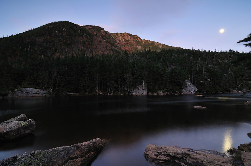 Moonlight illuminates Carter Dome beyond Lower Carter Lake in autumn. Carter Notch has a wild and remote feel to it, despite having an AMC hut nearby. Views in this neck of the woods are rugged and dramatic.