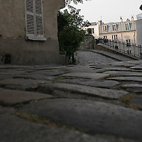 Rue Norvins, Montmartre, Paris, France.  Vue showing the cobblestone street in the village.  Typical Montmartre Architecture, shows louvered shutters and appartment buildings.