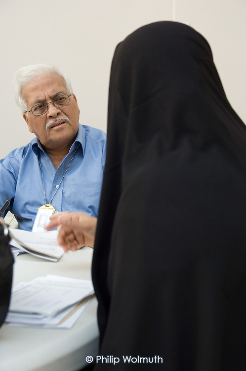 Labour Councillor Mushtaq Qureshi.advises a resident at a weekly surgery at the Beethoven Centre, Queens Park, West London.