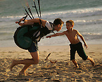 Retired marine Travis Haley and his son Travis Jr. (9) appears to slaying a dragon by managing his kite sail off the a windy beach in Kailua, Hawaii.