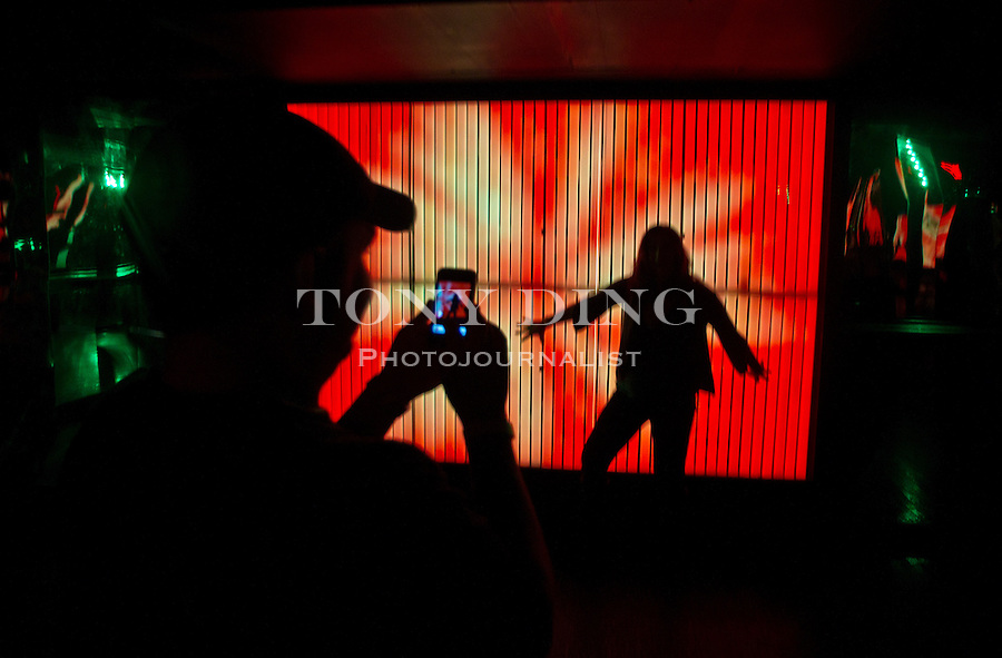 A couple take photos in front of a light wall display inside the Cavern Club, Saturday, Sept. 3, 2011 in Ann Arbor, Mich. (Tony Ding for The New York Times)