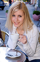 Modern woman in her 20s having lunch and coffee at cafe, Kiev, Ukraine