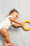 7 month old baby boy rolling on side as he grasps nubby yellow textured plastic ring full length