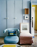 A contrast of seating - retro and traditional - against a series of built-in cupboards in the living room of this Italian apartment
