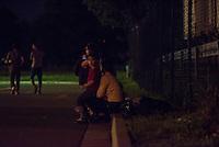 Wilkommensfest fuer Fluechtlinge im saechsichen Heidenau.<br /> Nachdem Polizei und politisch Verantwortliche vergeblich versucht hatten ein Wilkommensfest fuer Fluechtlinge mit dem Argument des Polizeilichen Notstands zu verbieten feierten hunderte Menschen zusammen. Fuer die Fluechtlinge waren Kleidungs- und Sachspenden nach Heidenau gebracht worden, die in Berlin, Dresden und anderswo gesammelt wurden.<br /> Zahlreiche Polizeikraefte waren zum Schutz des Festes im Einsatz.<br /> Im Bild: Die Unterstuetzerinnen sind wieder gegangen und Gefluechtete sitzen abends auf dem Parklplatz vor der Unterkunft.<br /> 28.8.2015, Heidenau<br /> Copyright: Christian-Ditsch.de<br /> [Inhaltsveraendernde Manipulation des Fotos nur nach ausdruecklicher Genehmigung des Fotografen. Vereinbarungen ueber Abtretung von Persoenlichkeitsrechten/Model Release der abgebildeten Person/Personen liegen nicht vor. NO MODEL RELEASE! Nur fuer Redaktionelle Zwecke. Don't publish without copyright Christian-Ditsch.de, Veroeffentlichung nur mit Fotografennennung, sowie gegen Honorar, MwSt. und Beleg. Konto: I N G - D i B a, IBAN DE58500105175400192269, BIC INGDDEFFXXX, Kontakt: post@christian-ditsch.de<br /> Bei der Bearbeitung der Dateiinformationen darf die Urheberkennzeichnung in den EXIF- und  IPTC-Daten nicht entfernt werden, diese sind in digitalen Medien nach §95c UrhG rechtlich geschuetzt. Der Urhebervermerk wird gemaess §13 UrhG verlangt.]