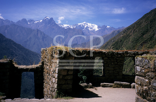 Inca Trail, Peru. Overgrown Inca walls with windows and doors at Winyay Wina. Valley and snowcapped peaks behind.