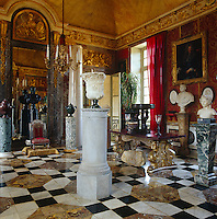 The red and gold main salon with its intricate geometric marble floors and ornate mouldings is an imposing reception room