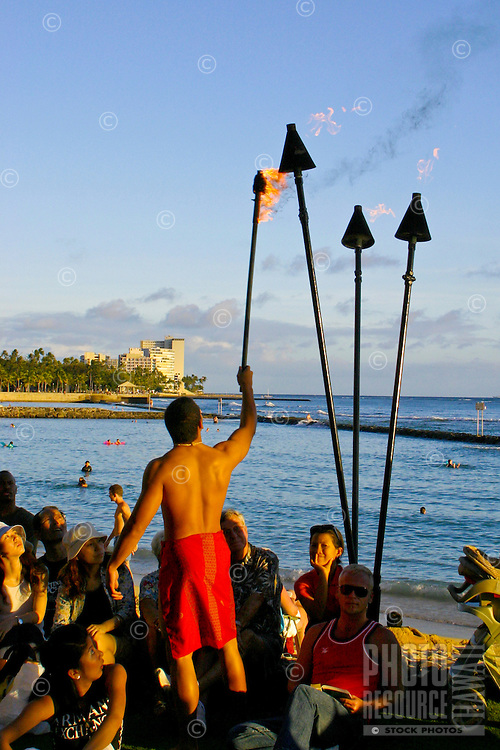 Here a Hawaiian man performs the Torchlighting Ceremony as tourist enjoy watching Hula Dancers of all ages perform at the Kuhio Beach Park stage under the Banyan Tree. A variety of music/chant and dance is performed at this weekly event. Located nea