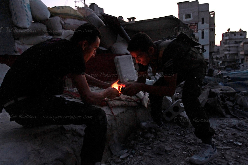 Free Syria Army soldiers light a home-made grenade to used against Assad forces during urban fighting in the al-Amaria district of Aleppo...© Javier Manzano..© Javier Manzano