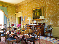 Lewis & Wood wallpaper with a floral pattern has been used in this dining room furnished with a Georgian dining table and chairs and a William IV sideboard