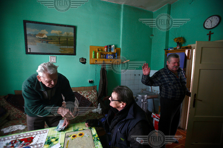 60 year old postman Jacek Serkiew delivers pension money to 94 year old Marek Grabowski. Jacek is celebrating his 40th year of being a postman..