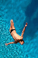 Aerial view of a male competition platform diver as he prepares for entry into the water.