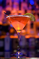 Still life photo of cocktail with colored lights blurred out in background.