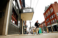 Max Blair and his husky, Artemis, walk by the 'We Will Get Through This Pittsburgh' sign posted outside of the Row House Cinemas in the Lawrenceville neighborhood on Monday March 16, 2020 in Pittsburgh, Pennsylvania. (Photo by Jared Wickerham/Pittsburgh City Paper)