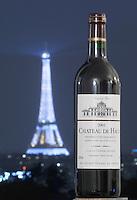 Eiffel Tower illuminated at night.  With a bottle of wine. Paris, France. Chateau de Haux, Bordeaux, France