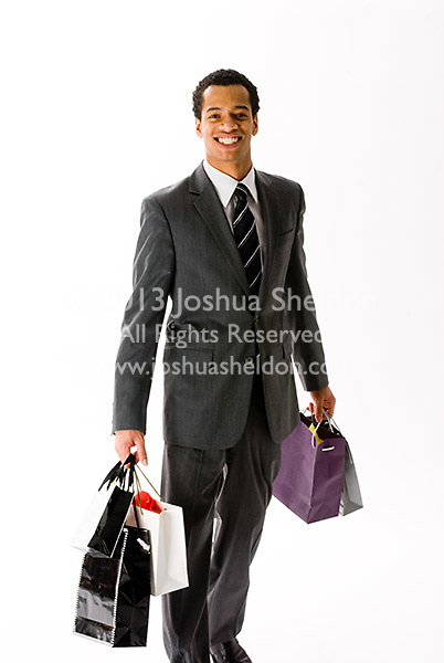 Young man wearing a business suit carrying shopping bags on white background