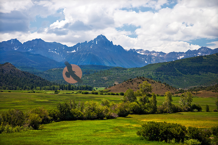 Green valley with steep rocky mountains in background