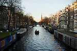 A lone boat on the Prinsengracht with the Westertoren of the Westerkerk in the background.
