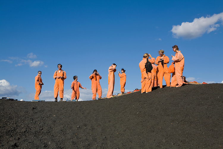 Backpackers put on their protective orange suits in preparation to board down the active volcano Cerro Negro, Nicaragua