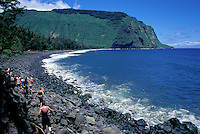 At the black-sand beach at Waipio, visitors coming back from a waterfall follow a rocky trail.