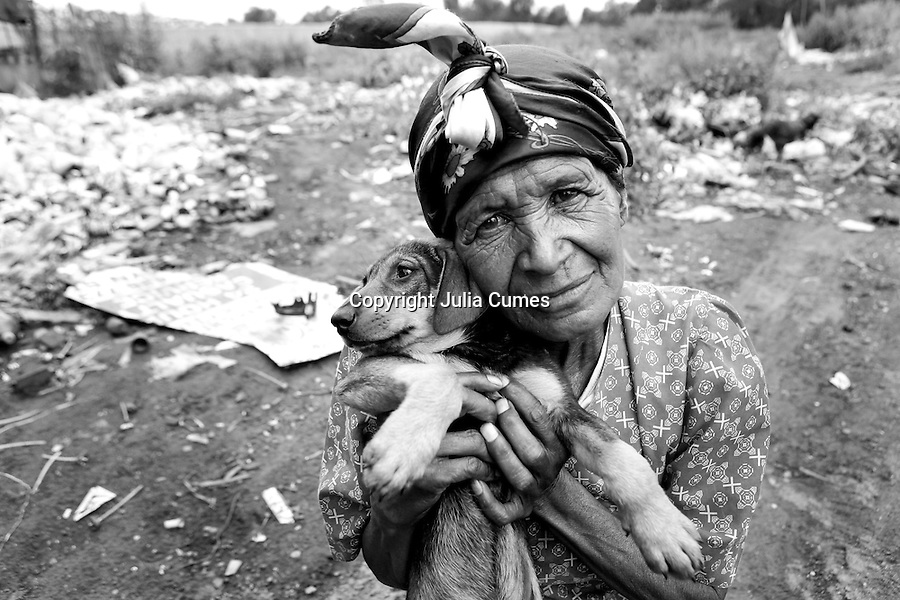 A woman is photographed with her puppy at the Randfontein Refuse Center on the outskirts of Johannesburg, South Africa.  She, like many others, lives in a small shanty and survives off the refuse brought in every day. Many residents sort and sell recyclable items and live off what edible food they can find thrown out by others.  IFAW's CLAW program, which provides veterinary services to cats and dogs in some of the poorest shantytowns outside of Johannesburg, regularly serves this area.  Through its mobile clinics, outreach programs and veterinary hospital, CLAW provides life-saving support to the community's animals every day.  2/21/12 Julia Cumes/IFAW