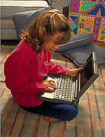 Young girl (age 7) works on laptop computer
