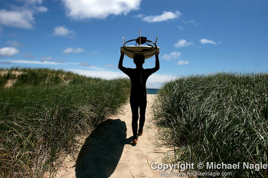 NANTUCKET - JUNE 19, 2005:  A young boy walks with his surf board to the beach on june 19, 2005 in Nantucket.  (PHOTOGRAPH BY MICHAEL NAGLE)