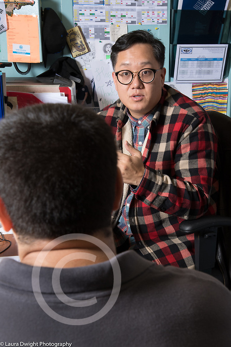 Education High School male teacher talking to male student, mentoring relationship