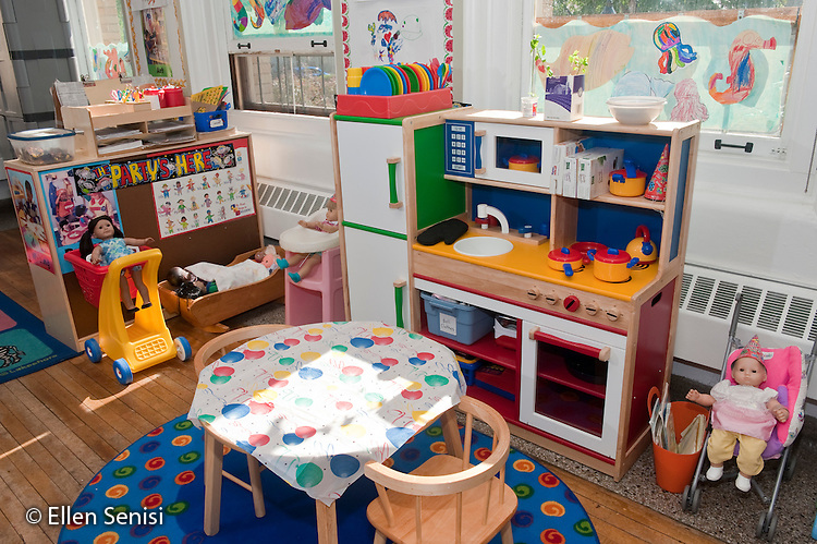 Schenectady, New York. Fulton Early Childhood Education Center (urban public school early childhood education center). Pre-K classroom. House play area with toy kitchen and dress up clothing in classroom. ID: AI-gPd. ©Ellen B. Senisi
