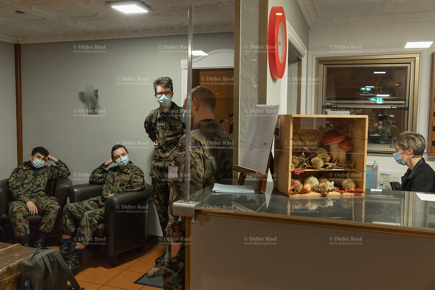 """Switzerland. Canton Ticino. Losone. Hotel Garni Tiziana. Four soldier dressed with camouflage uniforms stand in the hotel's lobby. The woman at the reception and the four men, all wear a mask to protect themselves from the coronavirus (also called Covid-19). Due to the spread of the coronavirus (also called Covid-19), the Federal Council has categorised the situation in the country as """"extraordinary"""". The army was called upon to provide its troops in terms of medical assistance. The militia soldiers from medical troops were called by the Swiss army for the first time since World War II. Under the country's militia system, professional soldiers constitute a small part of the military and the rest are conscripts or volunteers aged 19 to 34 (in some cases up to 50). The soldiers will be on duty the all day at the Ospedale Regionale di Locarno La Carità. 20.11.2020 © 2020 Didier Ruef"""