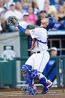 Florida Gators catcher Mike Rivera (4) steps on his mask as he tracks a foul pop against the Miami Hurricanes in the NCAA College World Series on June 13, 2015 at TD Ameritrade Park in Omaha, Nebraska. Florida defeated Miami 15-3. (Andrew Woolley/Four Seam Images)