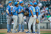 Myrtle Beach Pelicans pitching coach David Rosario has a meeting on the mound during the game against the Winston-Salem Dash at BB&T Ballpark on May 9, 2015 in Winston-Salem, North Carolina.  The Pelicans defeated the Dash 3-2 in 10 innings in the first game of a double-header.  (Brian Westerholt/Four Seam Images)