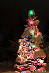 A lighted outdoor Christmas Tree flocked with a deep layer of fresh snow at night. Coeur d' Alene, Idaho.