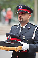 A Toronto police officer holds a hat during a parade commemorating police officers fallen on duty Sunday September 26, 2010.