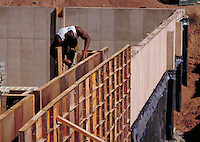 Concrete forms, wall structure and minority worker on scaffold, horz. West Hartford CT USA.