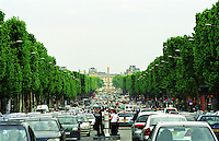 The Avenue des Champs Elysees in Paris with cars, looking down towards the Place de la Concorde with obelisk, the Louvre Museum and the Jardin des Tuileries garden park. Tourists pedestrians standing on a refuge in the center of the street. Paris, France Europe