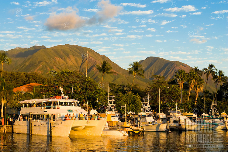 Lahaina boat harbor on a very calm day with the West Maui Mountains behind.