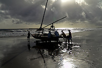 Brazilian fishermen (jangadeiros) push their boat towards the ocean at the sunrise in Uruaú, Ceará state, northeastern Brazil, 16 March 2004. Jangadeiros, working on a unique wooden raft boat called jangada, keep the tradition of artisan fishing for more than four hundred years. However, being a fisherman on jangada is highly dangerous job. Jangadeiros spend up to several days on high-sea, sailing tens of kilometres far from the coast, with no navigation on board. In the last two decades jangadeiros have been facing up the pressure from motorized vessels which use modern, effective (and environmentally destructive) fishing methods. Every time jangadeiros come back from the sea with less fish.