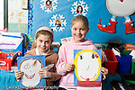 Education Elementary school Grade 2 two girls holding up self portraits of themselves as president art activity social studies horizontal