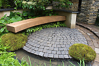 Patio of bluestone pavers, with curving bench, moss, ferns, stone pillars, wall, shaded garden