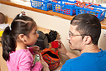 Education Preschool Headstart SEIT worker talking with girl in pretend play family area