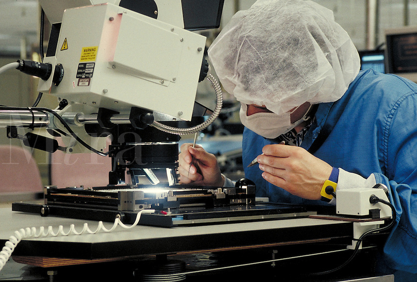 Employee inspecting computer chips in computer clean room, Amdahl Company, California. Computers. Technology. Electronics. Career. Occupation. California.