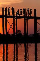 Myanmar, Burma, Mandalay, Amarapura.  Burmese Walking Home over the U Bein Bridge at the end of the day.  The teak footbridge is 200 years old, and 1300 yards long.
