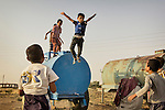 04/07/2015 -- Dibaga-Makhmur-, Iraq -- IDP kids jump from the tank of water while playing in Dibaga. The owner of the farm brings water to them every week more than once depending on their needs.
