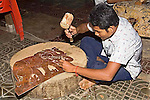 Cambodian young male_14 years old_uses hammer and nail to carve shadow puppet art from leather in Siem Reap_Cambodia