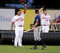 Members of the Rome Braves, including Cory Brownsten (30), center, and Greenville Drive, including Boss Moanaroa (29), left and Kevin Brahney (19), right, celebrate the end of a mock battle, attacking from opposite sides of the field, during a lengthy rain delay before a game on July 5, 2012, at Fluor Field at the West End in Greenville, South Carolina. (Tom Priddy/Four Seam Images)